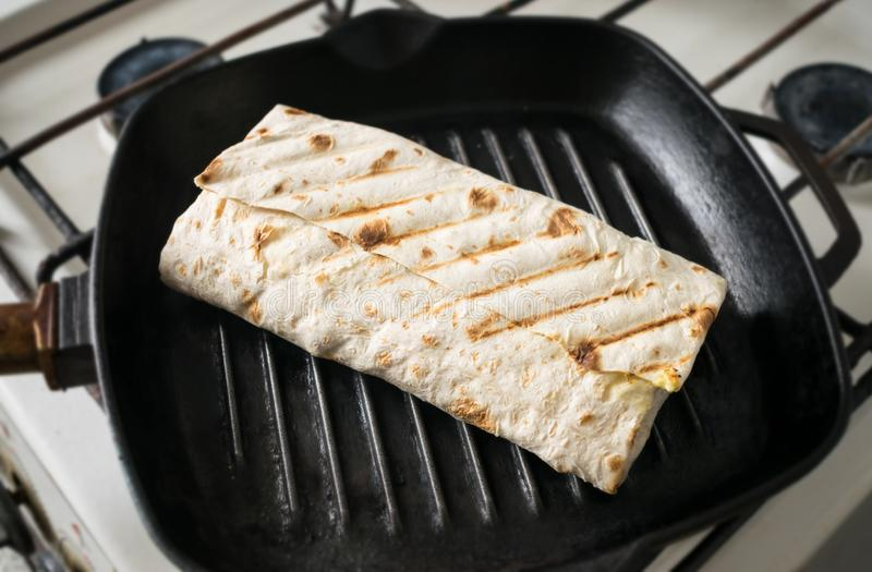 Roll of pita bread in a frying pan. Grilled rolls of bread lavash with roasted chicken and fresh vegetables. Picnic lunch, snack. royalty free stock photos