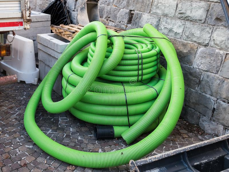 Roll of plastic pipe for road works. Protection of electric or telephone cables royalty free stock photos