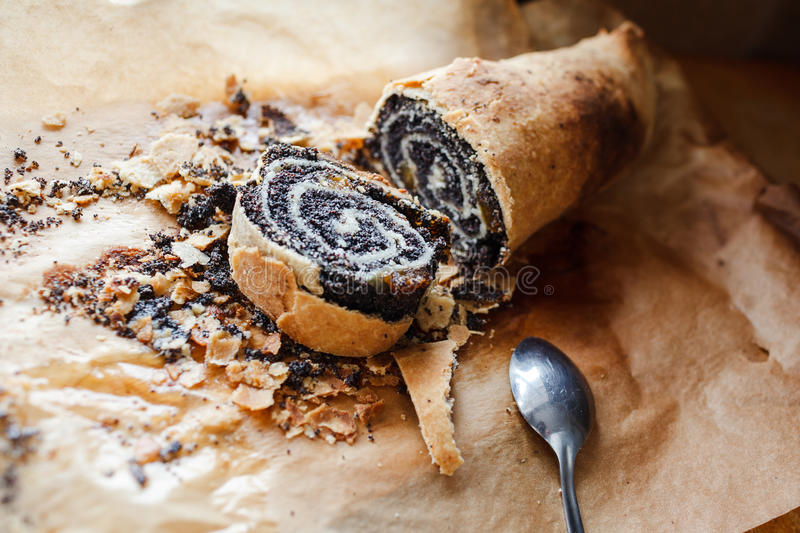 Roll with poppy seeds on baking paper stock images