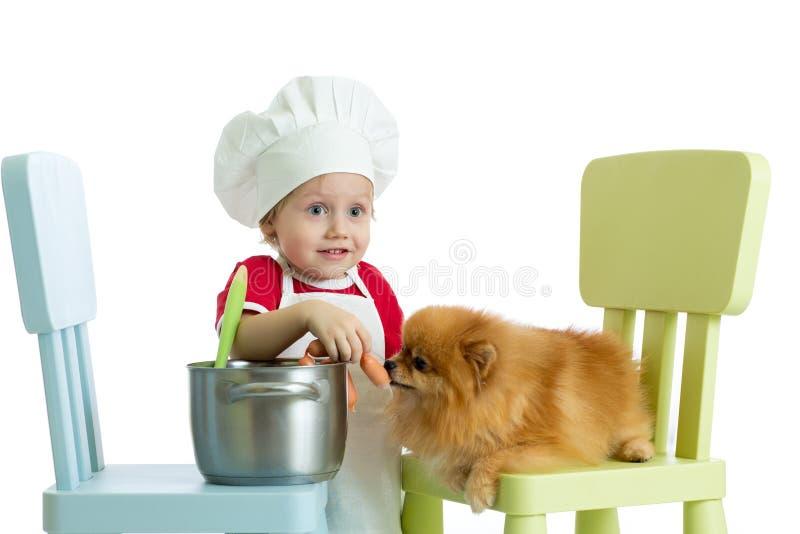 Roll-spela leken Ungepojken spelar kocken med hunden Barnet weared kocken matar Spitzvalpen arkivbilder