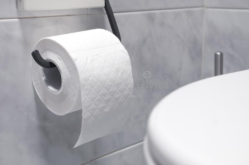 Roll of toilet paper in a tiled bathroom royalty free stock photography
