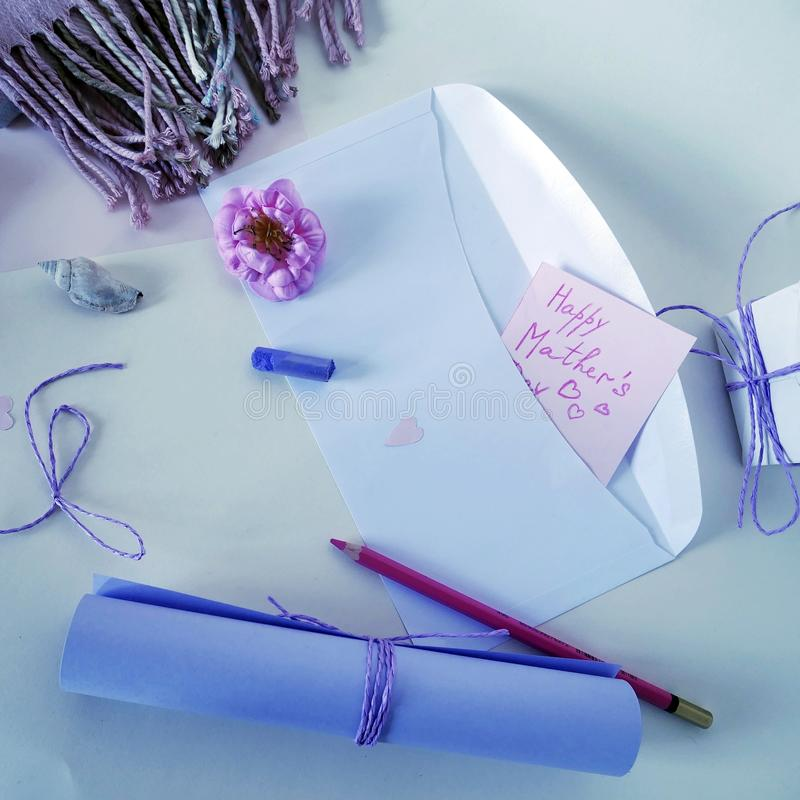 A roll of ultraviolet paper, a white envelope, a red pencil and a pastel crayon for congratulations on Mother`s Day royalty free stock photography