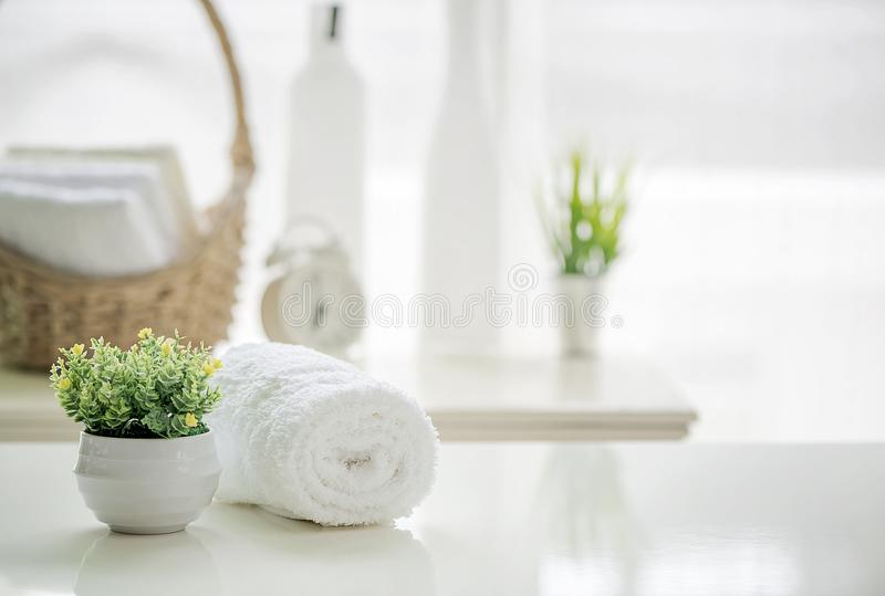 Roll up of white towels on white table with copy space on blurred living room background stock photo