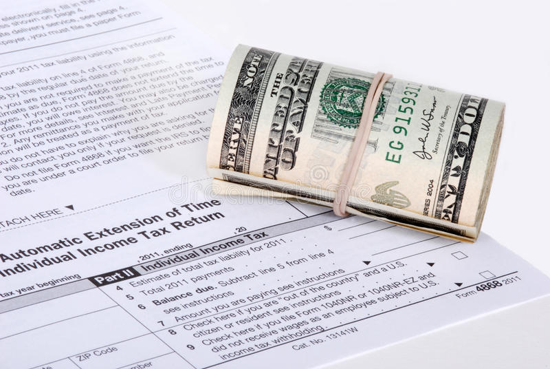 A roll of USD money near a tax form stock photography