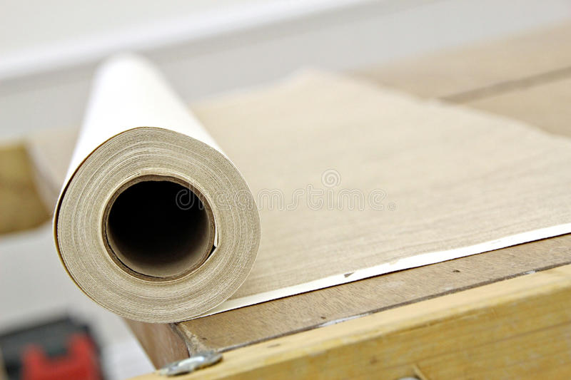 Roll of wallpaper on bench. Abstract photo of a roll of wallpaper on pasting bench royalty free stock images