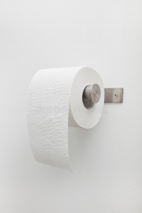 Roll of white toilet paper on a holder royalty free stock image
