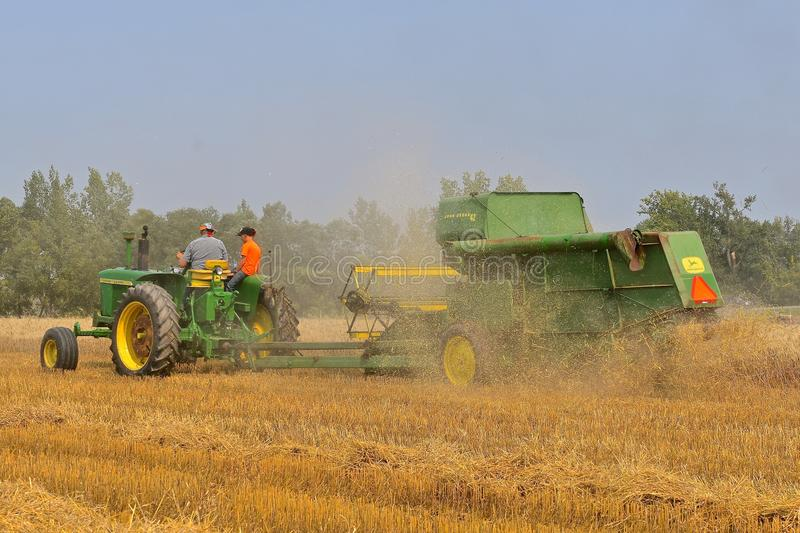 John Dere tractor and combine harvesting wheat. ROLLAG, MINNESOTA, Sept 2, 2017:A field demonstration of a John Deere tractor pulling a power take-off John Deer royalty free stock images