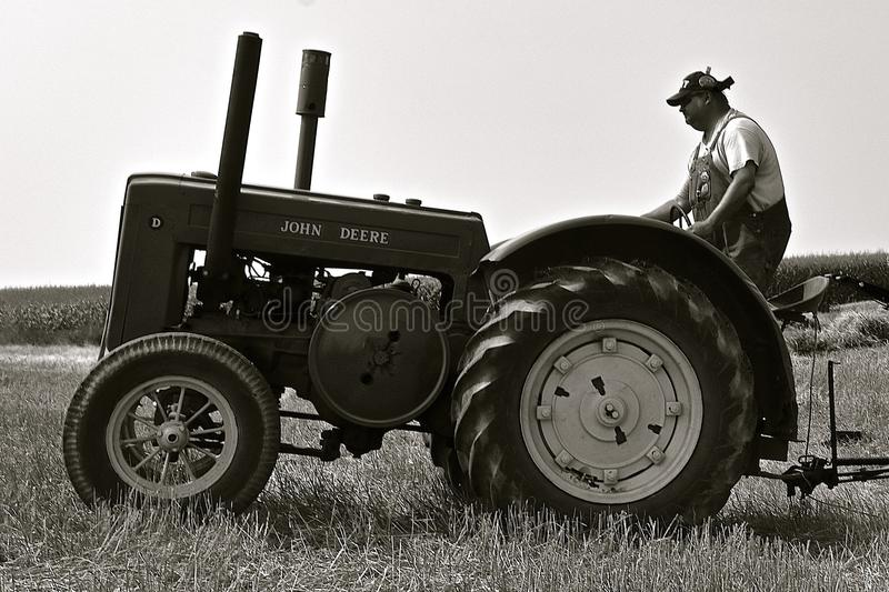 John Deere D tractor in a field. ROLLAG, MINNESOTA, Sept 2, 2017: An unidentified operator of an old D John Deere tractor participates in field demonstrations at stock images