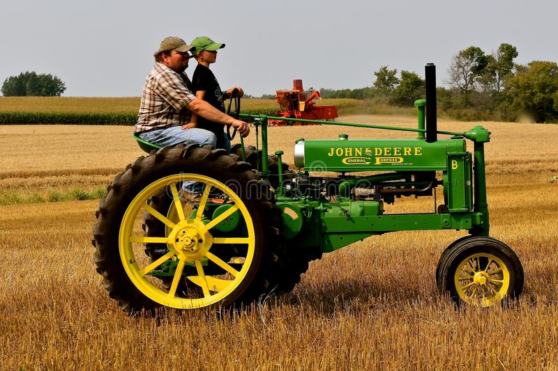 Father and Son driving a General Purpose John Deere tractor. ROLLAG, MINNESOTA, September 2, 2017: The father/son operators of the John Deere General Purpose royalty free stock images