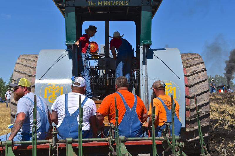Volunteers ride a gang plow pulled by a steam engine. ROLLAG, MINNESOTA, September 1, 2018: Unidentified volunteers ride a gang plow pulled by a steam engine in stock photos