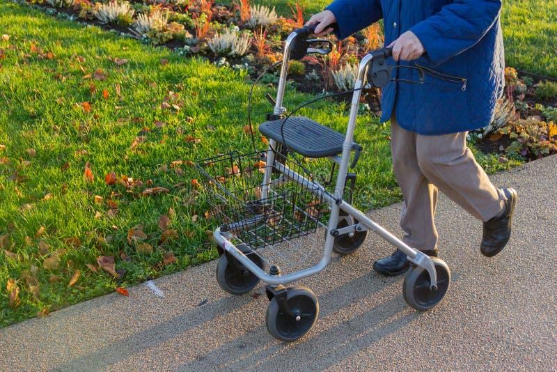 rollator και αναπηρική καρέκλα με τον πρεσβύτερο στο ιστορικό πάρκο στοκ εικόνες