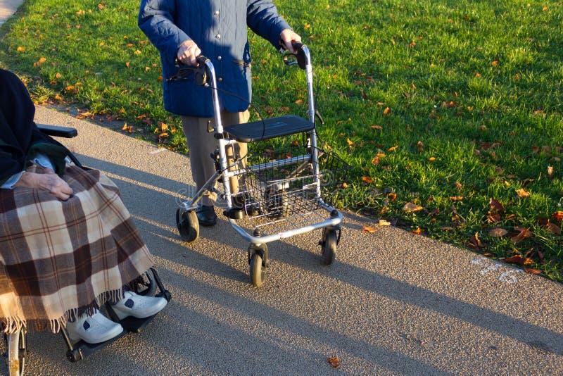rollator et fauteuil roulant avec l'aîné au parc historique photos libres de droits