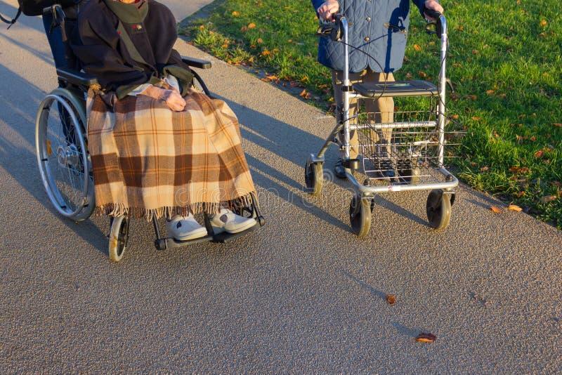 rollator et fauteuil roulant avec l'aîné au parc historique image libre de droits