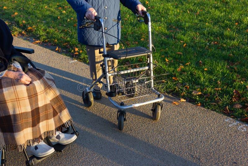 rollator et fauteuil roulant avec l'aîné au parc historique photo libre de droits