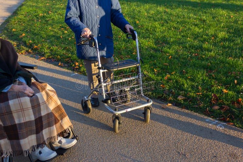 rollator et fauteuil roulant avec l'aîné au parc historique photo stock