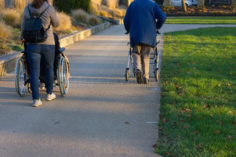 rollator et fauteuil roulant avec l'aîné au parc historique images stock