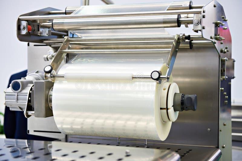 Rolle der Verpackungsfolie auf Maschinenlebensmittelfabrik stockfotos