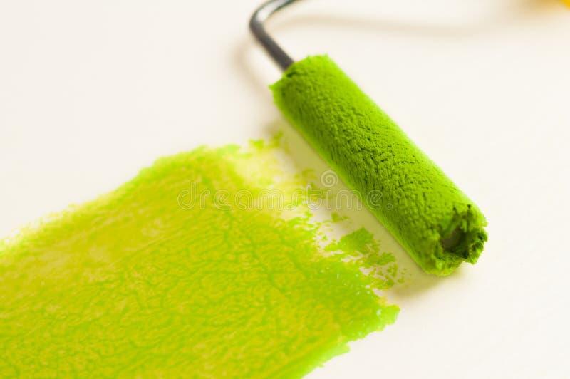 Rolle für Farbe und grüne Bahn auf Wand Reparieren Sie Konzept lizenzfreie stockfotos
