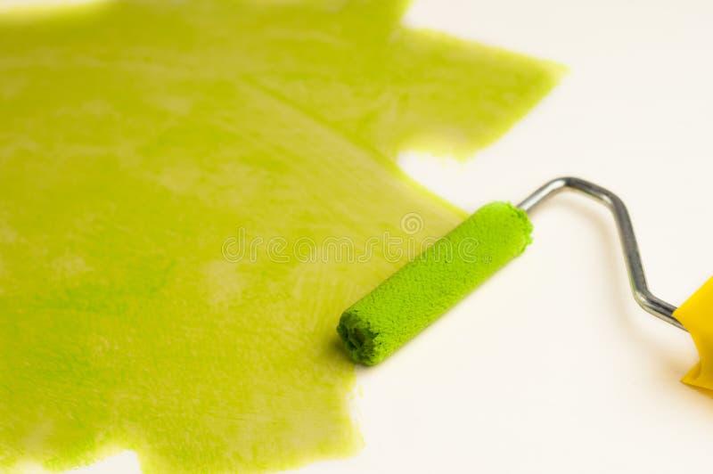 Rolle für Farbe und grüne Bahn auf Wand Reparieren Sie Konzept lizenzfreies stockfoto