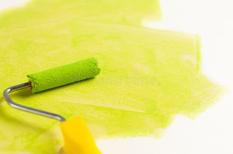 Rolle für Farbe und grüne Bahn auf Wand Reparieren Sie Konzept lizenzfreies stockbild