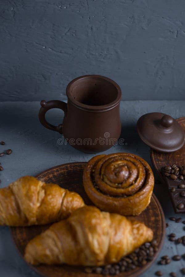 Rolle mit Zimt und H?rnchen auf einem grauen Hintergrund und ein Tasse Kaffee mit einem Schokoriegel stockfotos