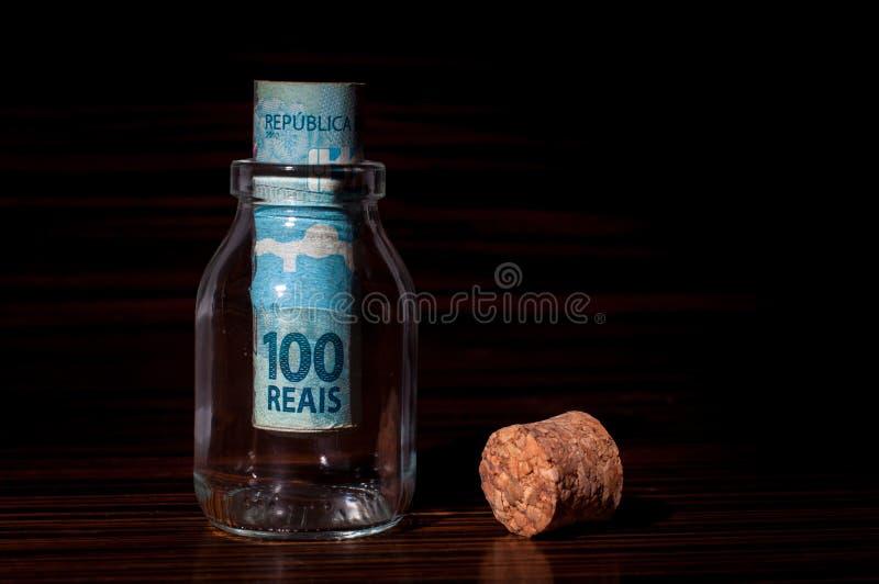 Rolle von 100 brasilianischen Reais-Banknoten innerhalb einer Flasche lizenzfreie stockfotografie