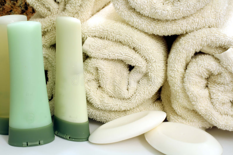 Rolled Bath Towels. This is an image of rolled bath towels with soap, shampoo, conditioner, and moisturizer royalty free stock images