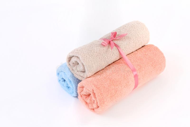 Rolled blue, pink and beige terry towels with a ribbon on a white background stock photos