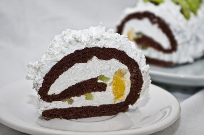 Rolled cake with whipped cream and fruits royalty free stock photography