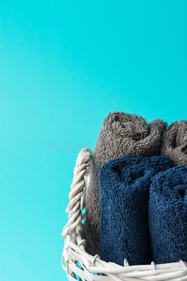 Rolled clean navy blue beige terry towels in white wicker basket turquoise wall background. Laundry ergonomic storage stock images