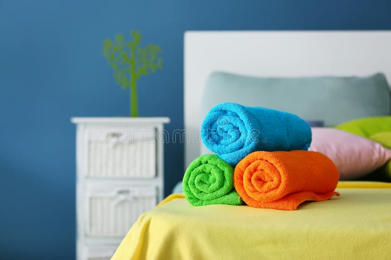 Rolled clean terry towels on bed royalty free stock photo