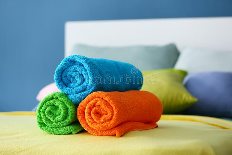 Rolled clean terry towels on bed royalty free stock image