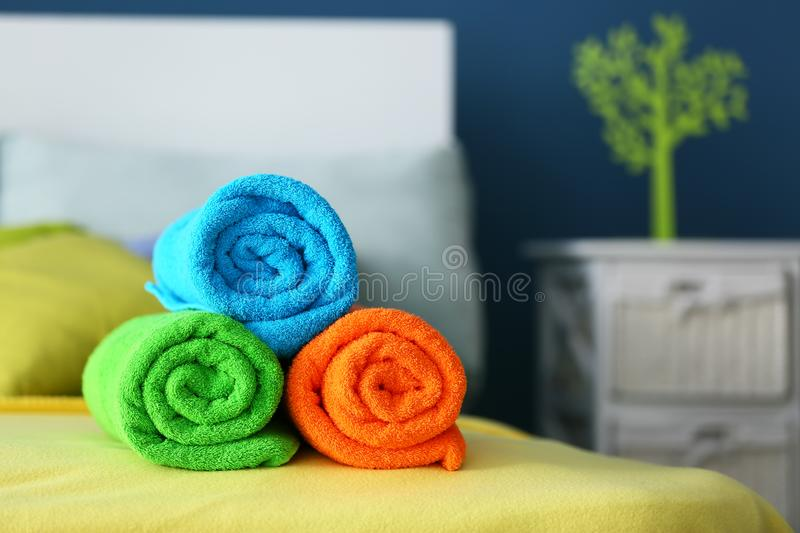 Rolled clean terry towels on bed stock images