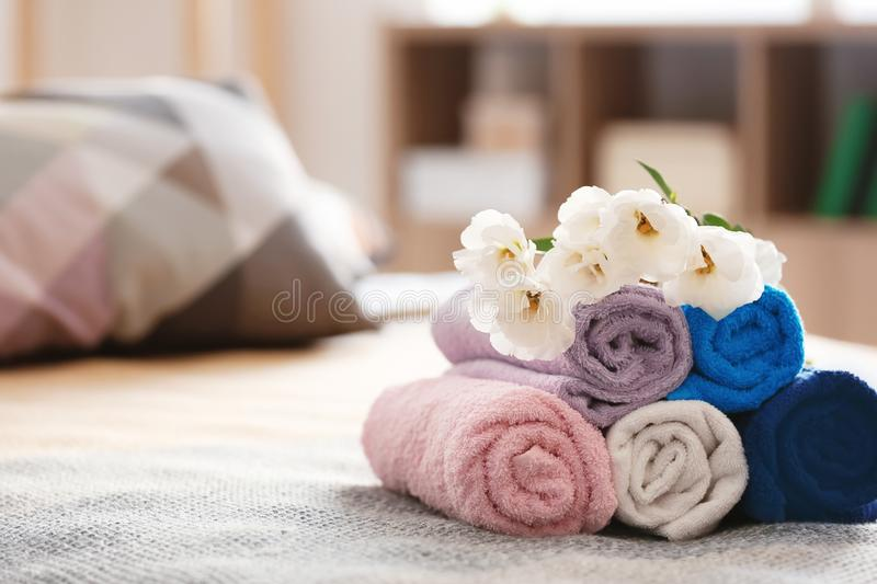 Rolled clean towels on bed royalty free stock image