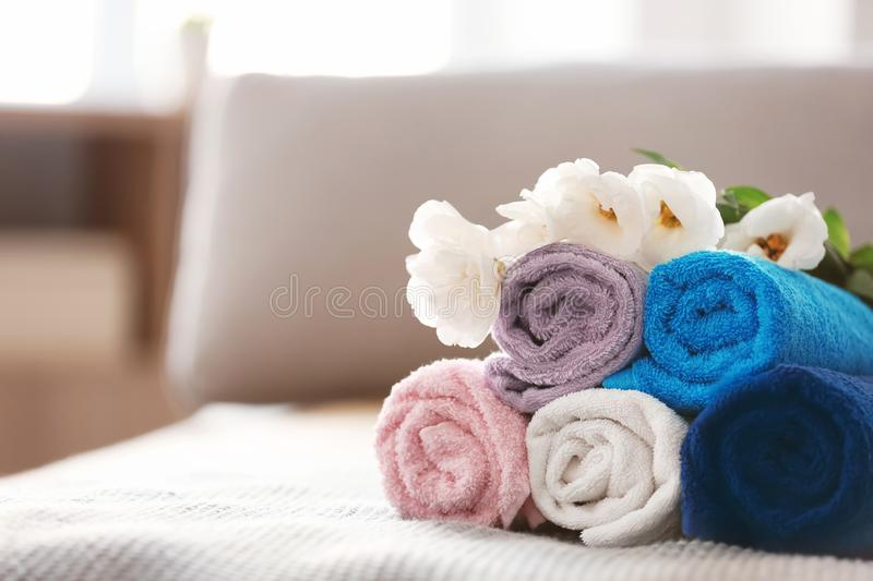 Rolled clean towels on bed stock photo