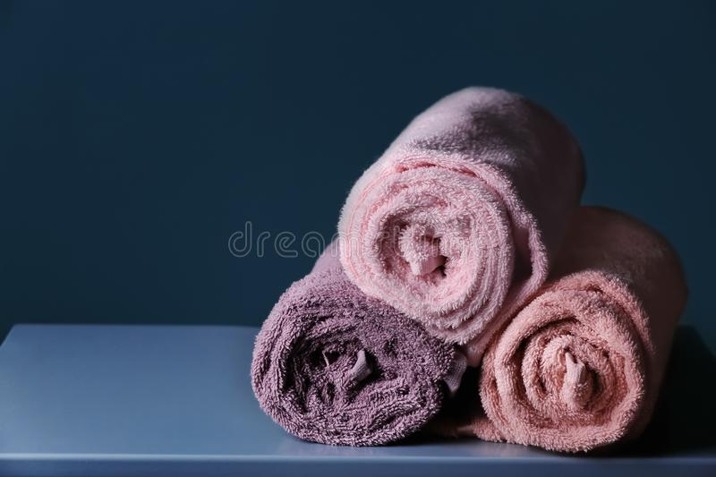 Rolled clean towels on table stock image
