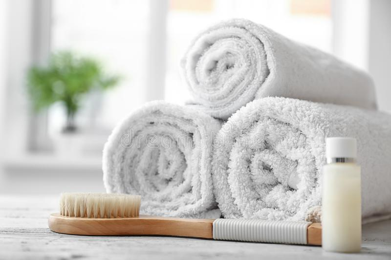Rolled clean white towels, cosmetic and brush on table indoors royalty free stock image