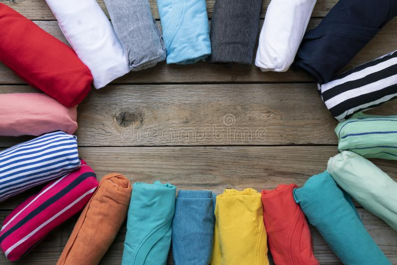 Rolled colorful clothes set in circle shape on woode stock photo