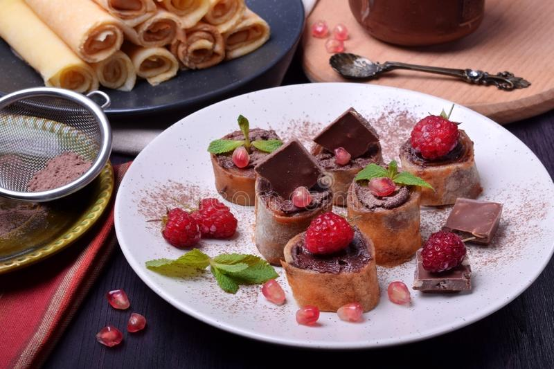 Rolled crepes with chocolate paste topped with raspberries, pomegranate, mint and chocolate pieces royalty free stock photo