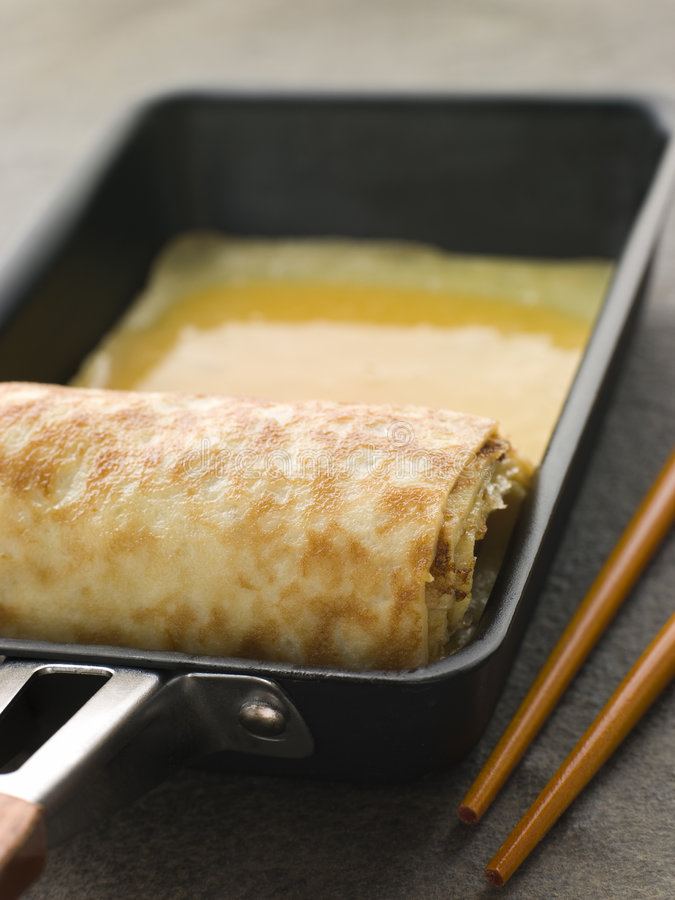 Rolled Dashi Omelette in a Square frying Pan. With chopsticks stock image
