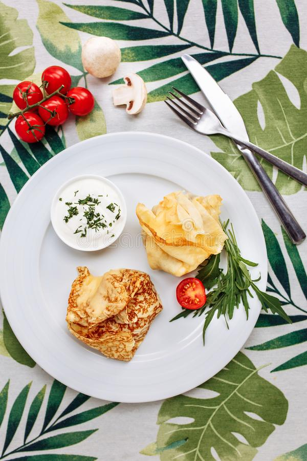 Rolled Delicious Crepes stuffed with chicken and mushrooms on the white plate serving with sour cream. Pancake is a flat royalty free stock photos