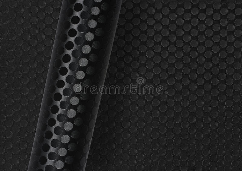 Rolled dotted dark surface. Rolled dark round dotted surface over same full frame textured background stock photography