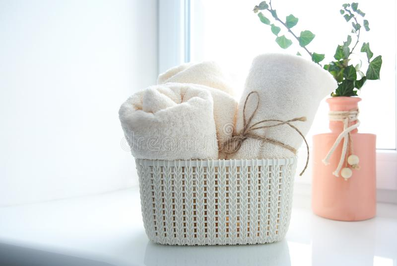 Bath towels in basket on window sill empty copy space royalty free stock photo