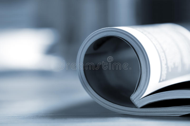 Rolled Magazine. Rolled glossy magazine on a table, with coffee cup behind. Very shallow depth of field, blue tone