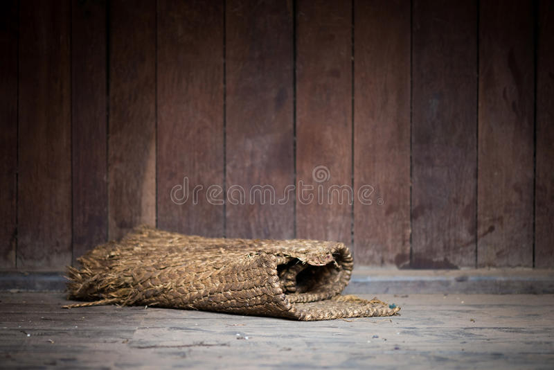 Rolled mat. Old rolled mat on the floor, wooden wall background stock photography