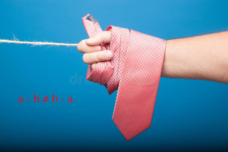 Rolled necktie in a hand of a man. With my hand I have wrapped a classic tie, there is also a rope for hanging clothes, on a plain background. The tie is a stock photo
