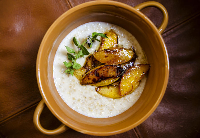 Rolled oats porridge. Breakfast with oats porridge, mint and caramerized peaches royalty free stock photos