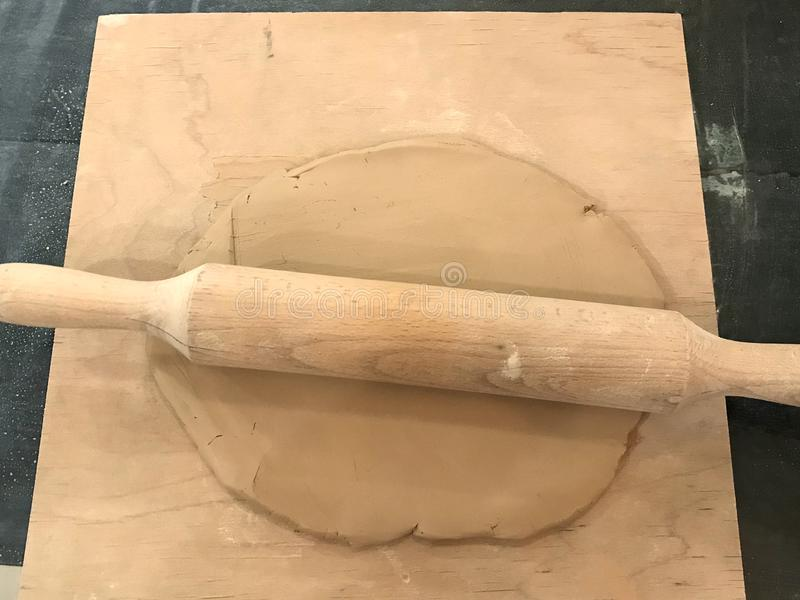 Rolled piece of pottery clay with a wooden rolling pin on a board on a black work table. Top view.  royalty free stock images