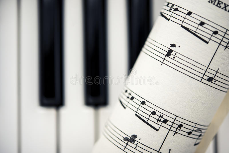 Vintage Sheet Music With Piano Keys. A rolled piece of vintage sheet music containing handwritten musical notes, as well as the original score, in front of a royalty free stock photos