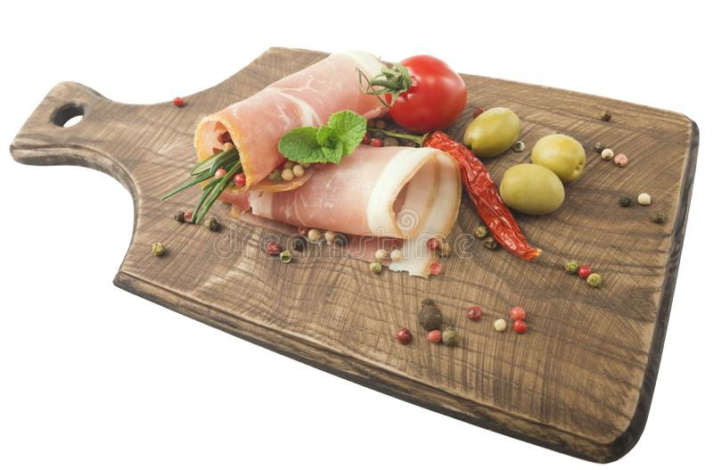 Rolled slices of ham on a wooden board royalty free stock photos